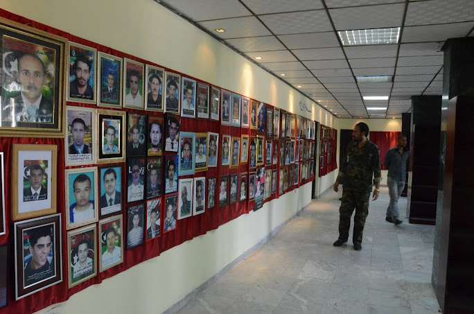 Photos of men, accompanied by Arabic text, displayed on red fabric on a wall.